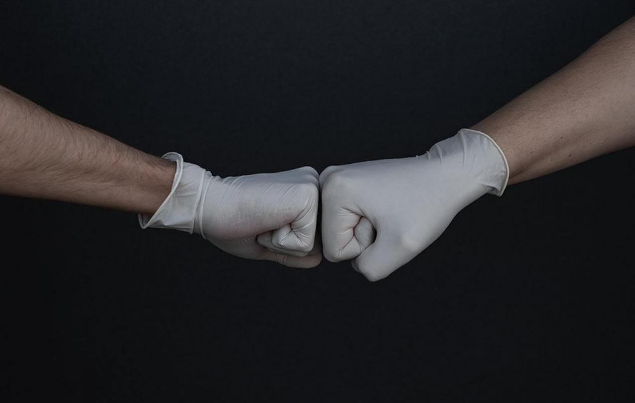 Two hands with light skin wearing medical gloves do a fist bump