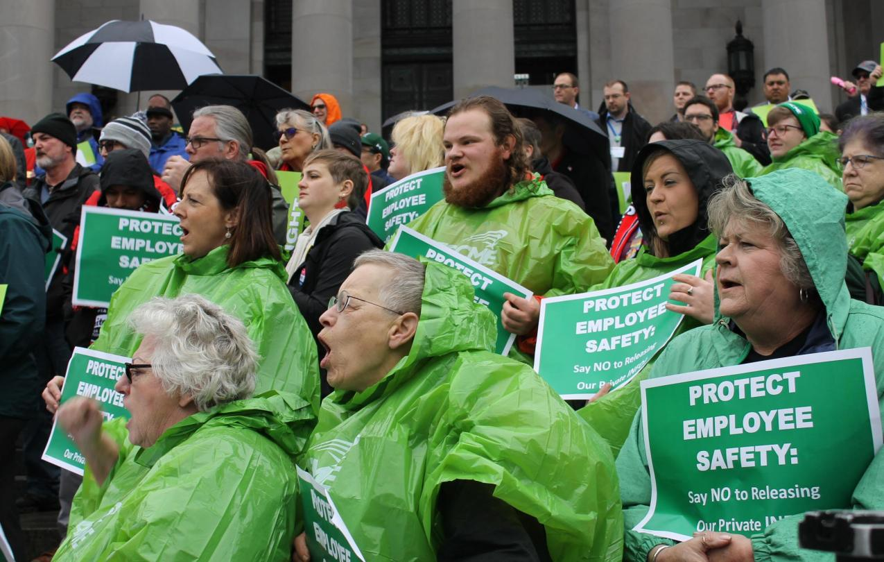 WFSE union members in green rain ponchos hold protest signs about protecting private info during a rally on the Olympia Capitol steps.