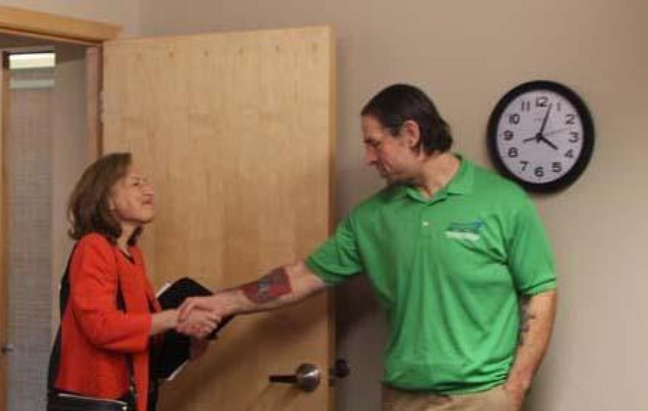 Congressperson Kim Schrier enters a door and shakes hands with WFSE President Mike Yestramski