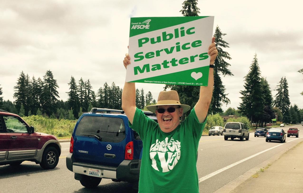 "Tim Hughes holds up a sign saying ""Public Service Matters"""