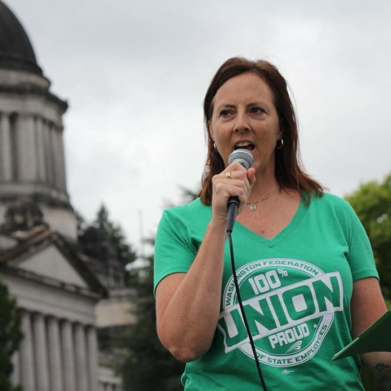 Picture of Leanne Kunze holding a microphone at a rally.
