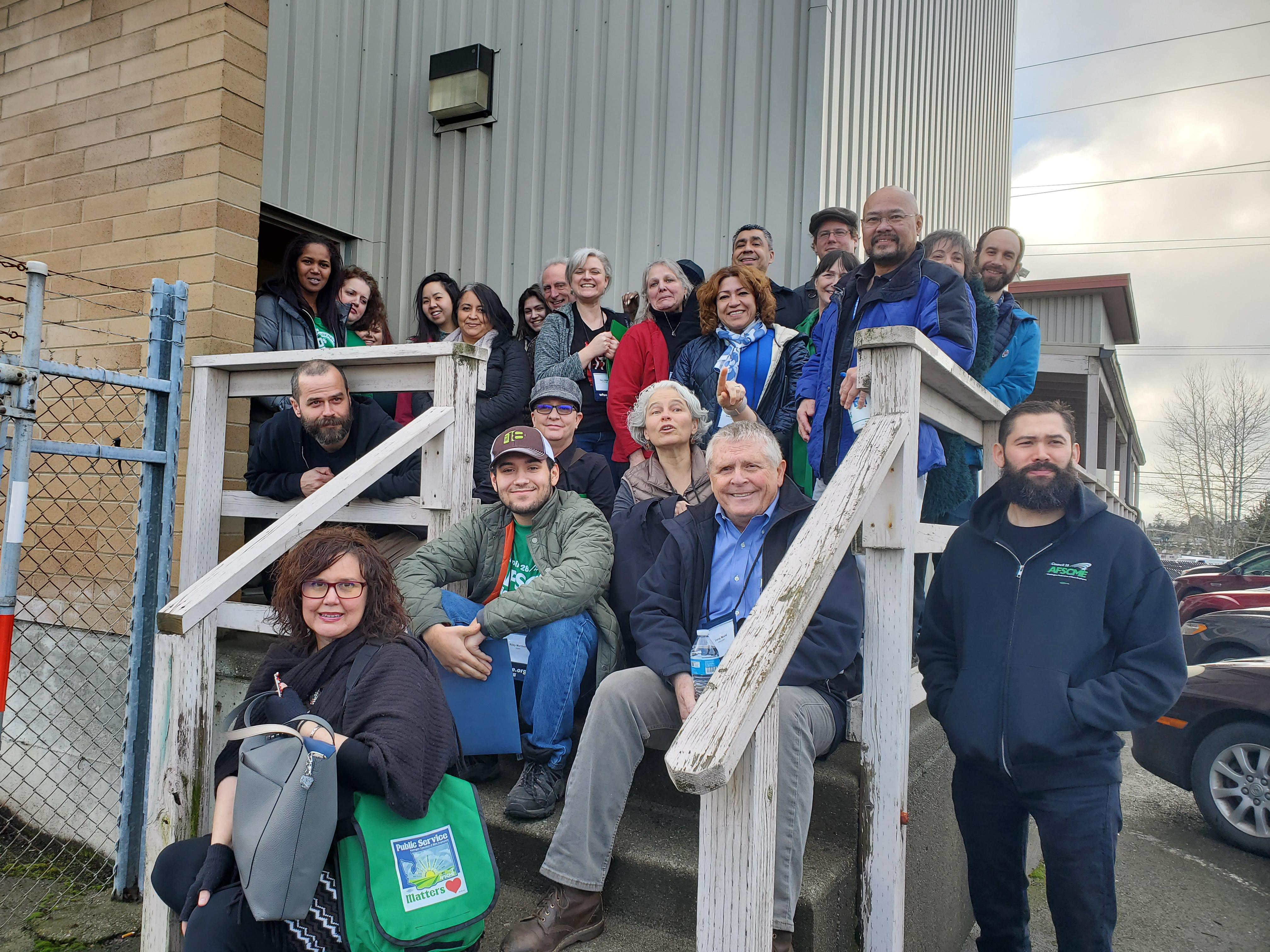 A group of WFSE members and staff gather outside on a cloudy day for a photo during the Interpreters United organizing blitz.