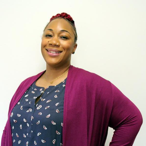 A headshot of WFSE Vice President Andrea Vaughn smiling in a pink sweater