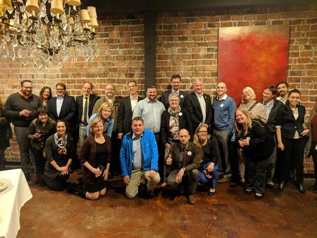 A group of the Washington Association of Assistant Attorneys General (AWAAG) members and WFSE staff poses in front of a brick wall.