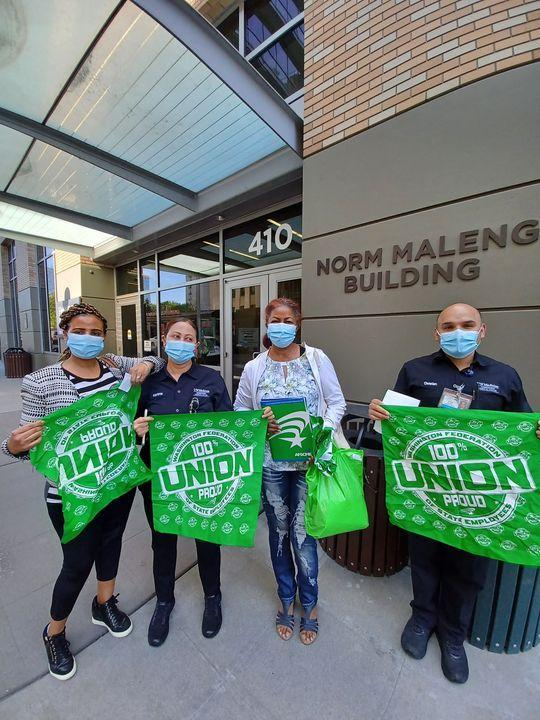 WFSE members & Maleng Cafe employees Ghenet Habtemnichael, Marianna Tereko, Aster Morrow, and Christian Cisneros each hold WFSE green items- three large bandanas and a folder outside the Norm Maleng Building. They are wearing masks.